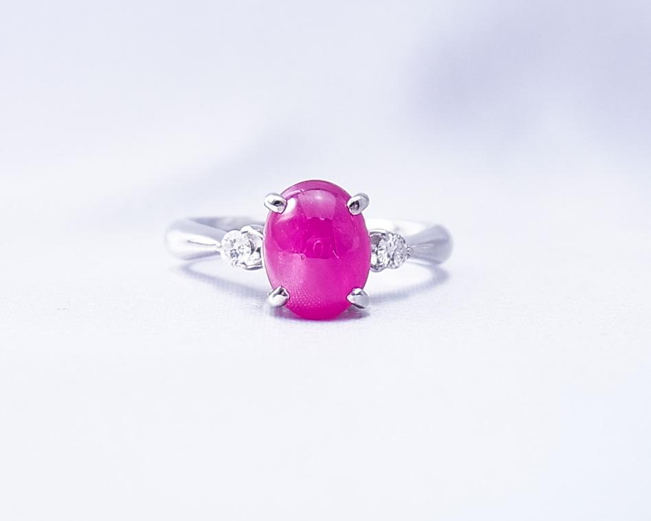 カボションカットルビーの左右に小さなダイヤモンドのついた指輪